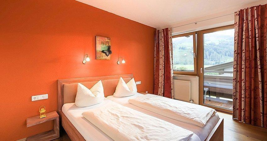 Schlafzimmer mit Balkonzugang und Doppelbett