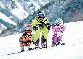Mann mit Kindern auf der Skipiste
