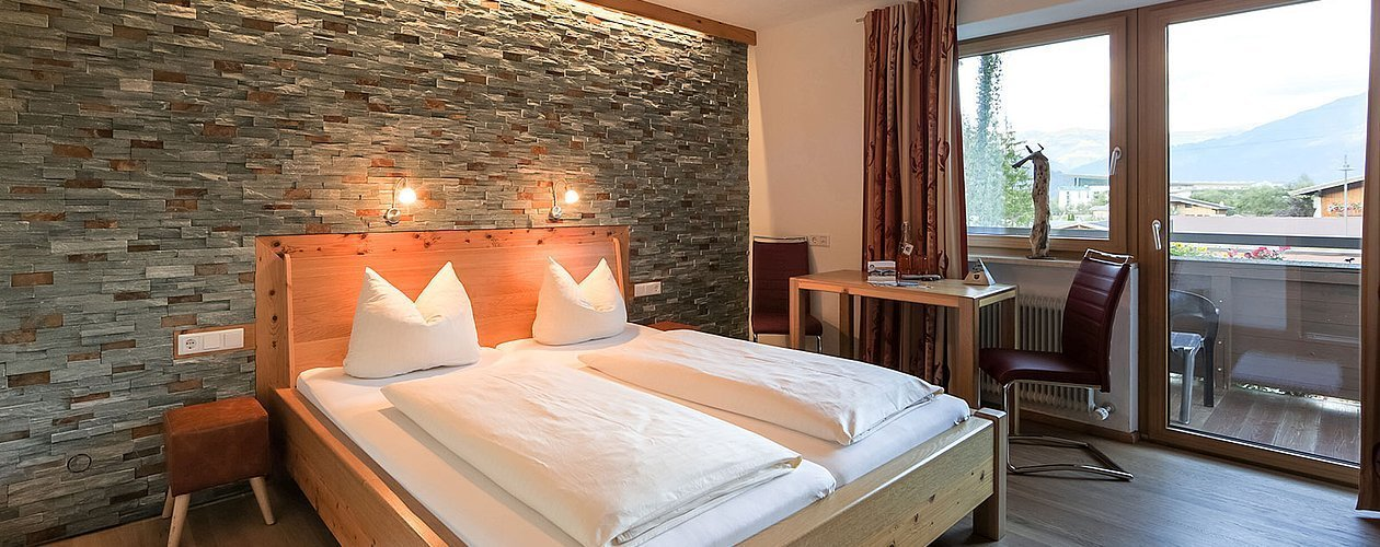 Schlafzimmer mit Doppelbett und Schreibtisch sowie privatem Balkon